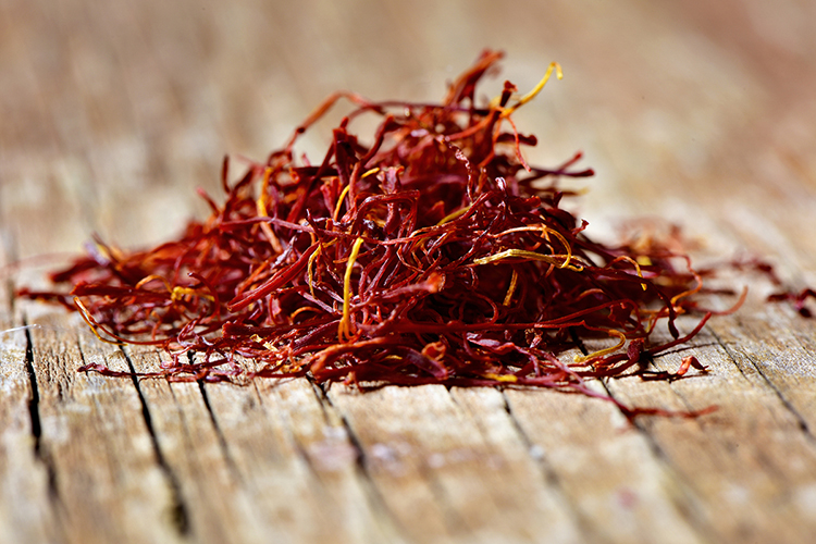 a pile of saffron threads on a rustic wooden table