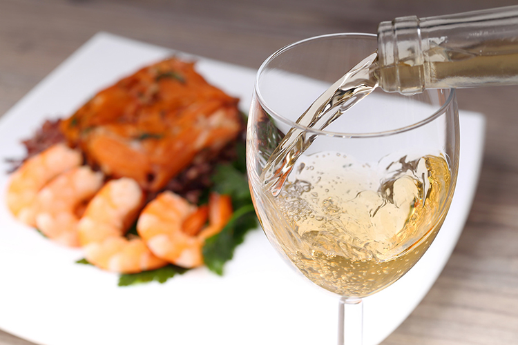 Pouring white wine and seafood background