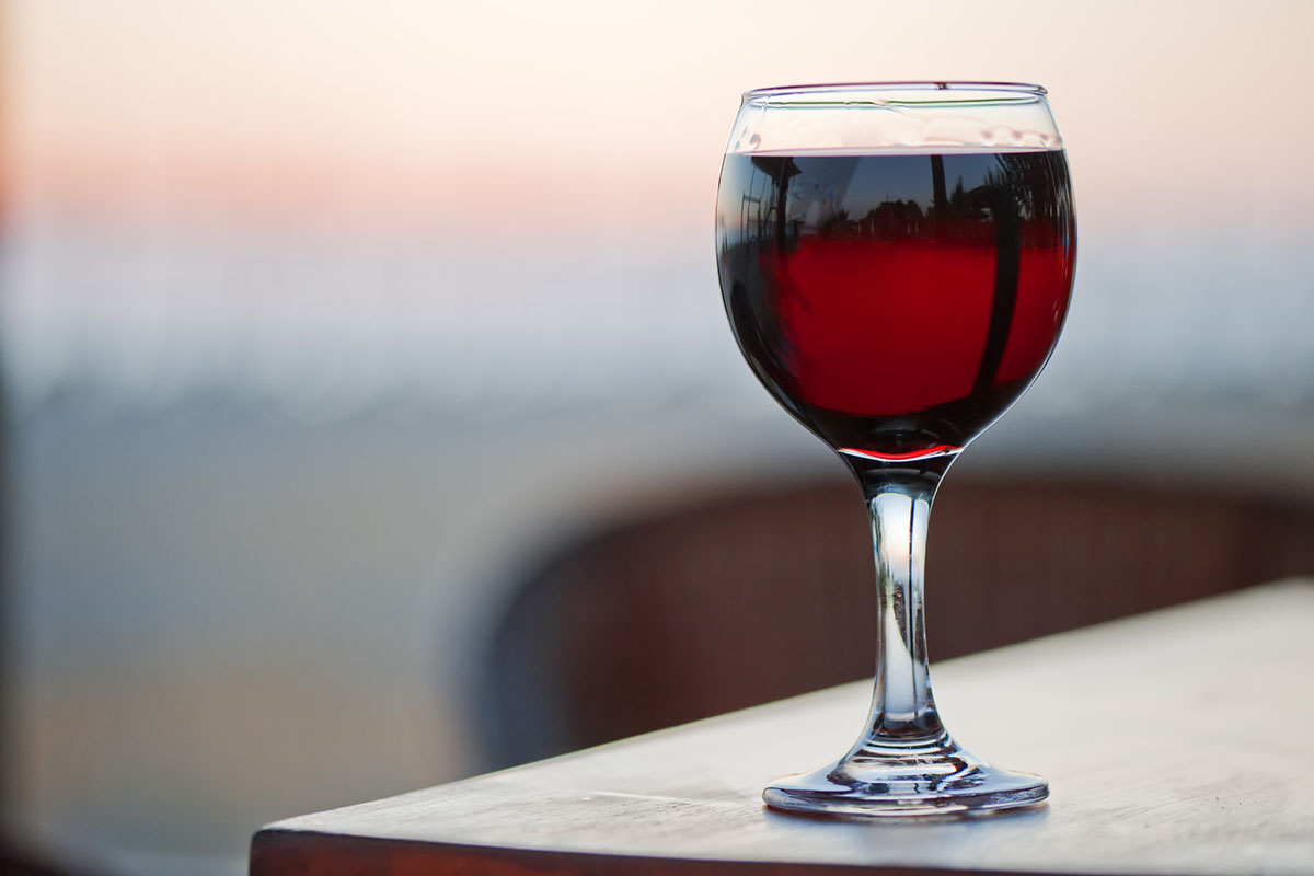 A glass of red wine at sunset.; Shutterstock ID 127093049; PO: aol; Job: production; Client: drone