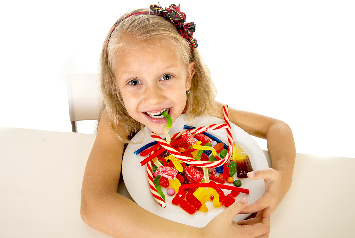 pretty happy Caucasian female child eating dish full of candy holding the dish in sweet sugar abuse dangerous diet and unhealthy nutrition concept isolated on white background