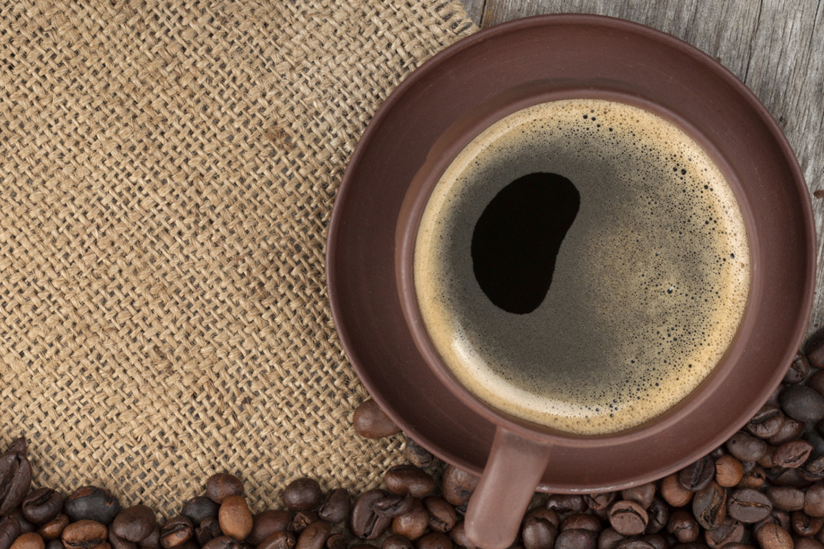 Coffee cup and beans on wooden table