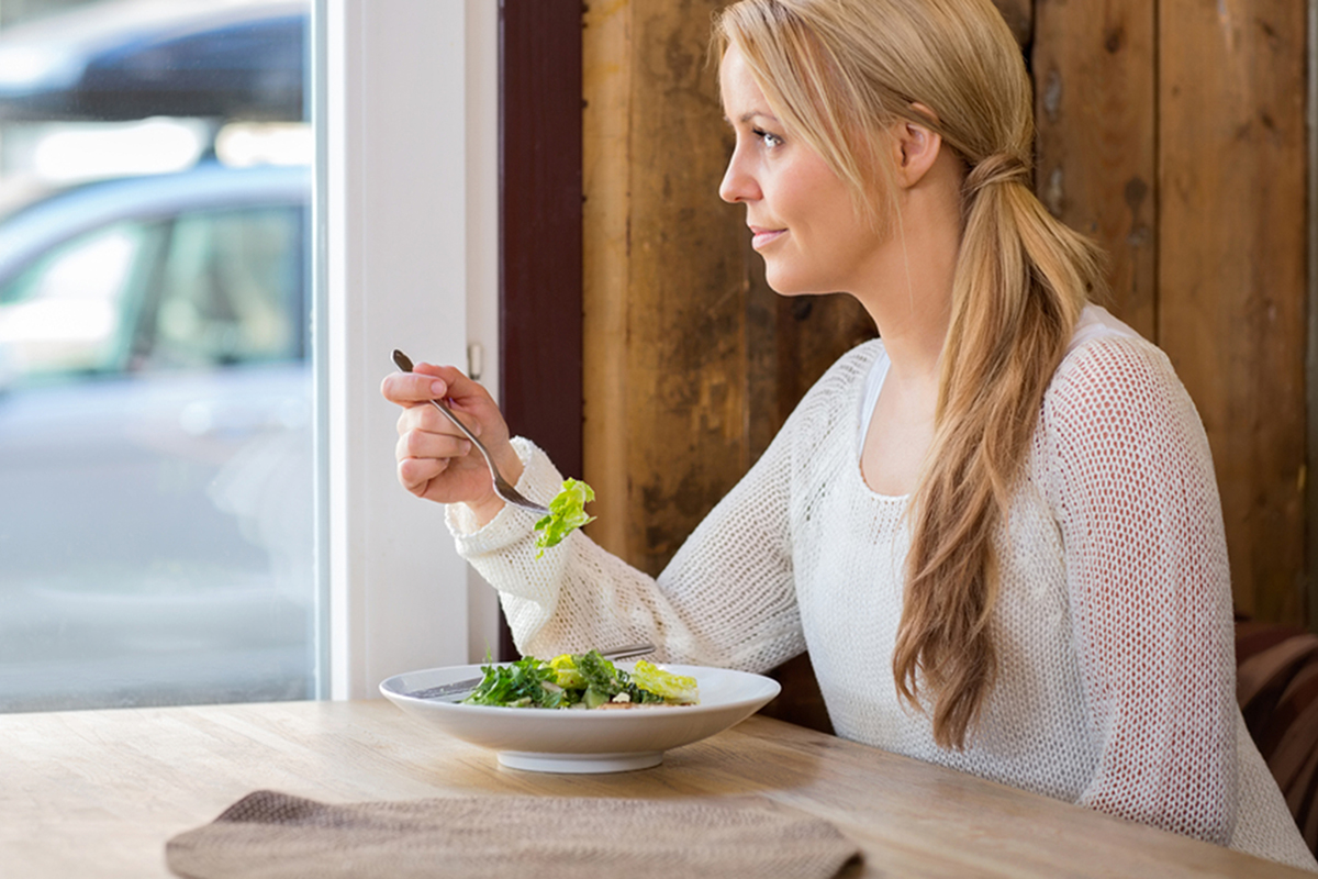 Young woman looking through window while eating salad in restaurant; Shutterstock ID 146229149; PO: todya.com